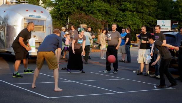 A crowd of people watching a game of foursquare at an outdoor party